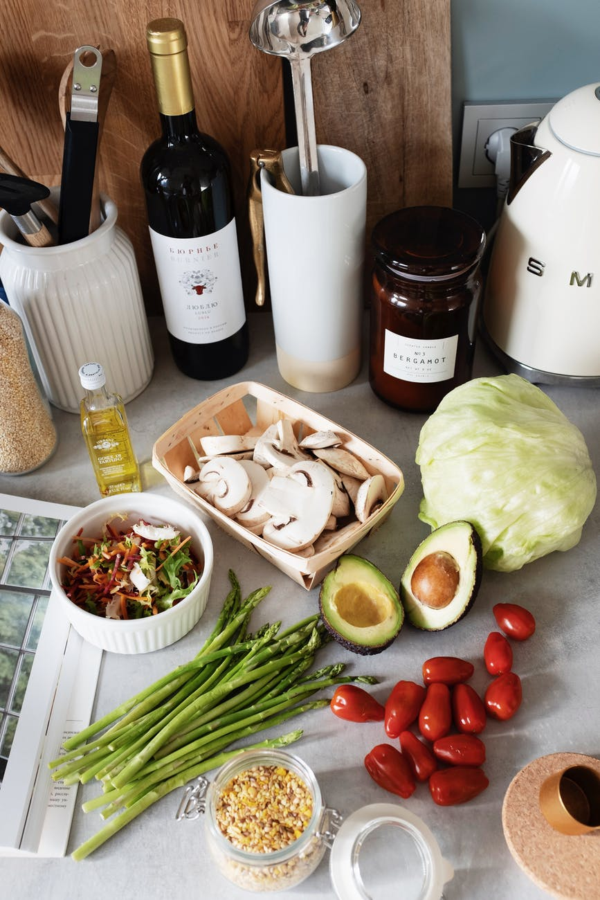 fresh vegetables and ingredients for recipe near oil and dishware on cozy kitchen